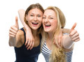 Two young happy women showing thumb up sign are hugging and isolated over white Stock Images