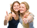 Two young happy women showing thumb up sign are hugging and isolated over white Royalty Free Stock Photography
