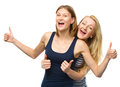 Two young happy women showing thumb up sign using both hands isolated over white Stock Images