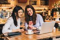 Two young happy women are sitting in cafe at table in front of laptop, using smartphone and laughing. Royalty Free Stock Photo