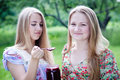 Two young happy young women eating strawberry jam on summer green outdoors background pretty teenage girls Royalty Free Stock Photos
