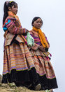 Two young hmong women show and wait at sunday market bac ha vietnam circa march in colorful traditional dress against white sky Stock Photos