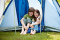 Two young kids sitting in front of a tent blue Stock Photos