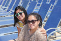 Two young ladies one teenager and mid s asian or filipina wearing sunglasses sitting on lounge chairs in a resort beautiful happy Royalty Free Stock Images