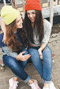 Two young longboarding girl friends happy funky sitting together on longboard and having fun outdoors lifestyle Royalty Free Stock Image