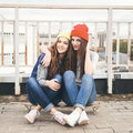 Two young longboarding girl friends sitting together on longboard and having fun outdoors lifestyle Stock Image