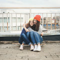 Two young longboarding girl friends sitting together on longboard and having fun outdoors lifestyle Stock Images