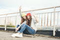 Two young longboarding girl friends sitting together on longboard and waving hands outdoors lifestyle Stock Photos