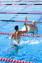 Two young male swimmers giving high-fives in swimming pool Royalty Free Stock Photo
