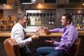 Two young man talking at counter. Royalty Free Stock Photo
