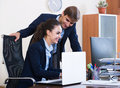 Two young managers using laptop at work smiling russian in office Stock Photo