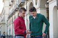 Two Young Men Looking Down at Cell Phone Outdoors Royalty Free Stock Photo