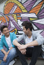 Two young men sitting on their skateboards and hanging out in front of a wall with graffiti Royalty Free Stock Image
