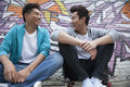 Two young men sitting on their skateboards and hanging out in front of a wall with graffiti Royalty Free Stock Photo