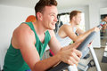 Two young men training in gym on cycling machines together wearing fitness clothing Stock Image