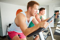 Two Young Men Training In Gym On Cycling Machines Together Royalty Free Stock Photo