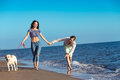 Two young people running on the beach kissing and holding tight with dog Royalty Free Stock Photo