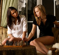 Two young and sexy girls are playing chess Stock Photos