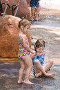 Two young sisters playing water together enjoying fun summer afternoon Stock Photo