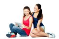 Two young sitting women looking in pad beautiful Stock Photography