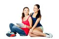 Two young sitting women with pad beautiful Royalty Free Stock Photos