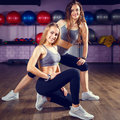 Two young smiling girl posing in fitness center Royalty Free Stock Photo