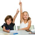 Two young students raising hands at desk. Stock Image