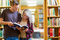 Two young students reading book in the library against bookshelves Royalty Free Stock Images