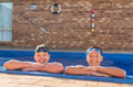 Two young swimmers happy in their private inground pool Stock Images