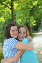 Two young teenage friends hugging pretty girl another with lovely smiles on their faces outdoors in a wooded park Royalty Free Stock Photos