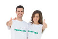 Two young volunteers giving thumbs up on white background Royalty Free Stock Photos
