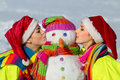 Two young woman kissing a snowman Royalty Free Stock Photography
