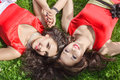 Two young woman lying on grass women in a luxurious red dresses the Stock Photo