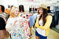 Two young women at apparel clothes shopping with shirt or blouse during garments clothing store Royalty Free Stock Images