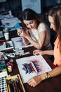 Two young women attending aquarelle painting classes for adults at art school. A girl showing her artwork to friend. Royalty Free Stock Photo