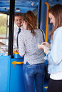 Two young women boarding bus and buying ticket from driver Stock Image