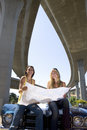 Two young women on bonnet of car looking at road map beneath overpass smiling portrait low angle view Stock Images