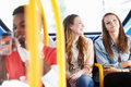 Two young women on bus journey together having a chat Stock Photo