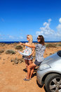 Two young women with car look at map Royalty Free Stock Images