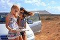 Two young women with car look at road map mountain landscape in background Stock Photos