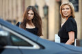 Two young women at the car walking on parking Royalty Free Stock Image