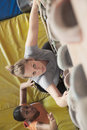 Two young women climbing in an indoor climbing gym directly above Stock Photo