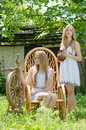 Two young women in country yard with spinning wheel and rock chair girls Royalty Free Stock Image
