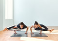 Two young women doing yoga asana eight-angle pose Royalty Free Stock Photo