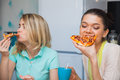 Two young women eat pizza. Girls taste italian traditional food