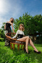 Two young women fashion portrait posing in garden outdoor Stock Photography
