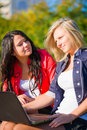 Two young women friends outdoors with a laptop Stock Images