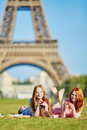 Two young women having picnic near the Eiffel tower in Paris, France Royalty Free Stock Photo