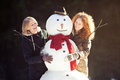 Two young women hugging snowman smiling pretty girls posing with a in forest focus on Stock Image