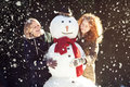 Two young women hugging snowman smiling pretty girls posing with a in forest it s snowing dark background focus on Stock Photos